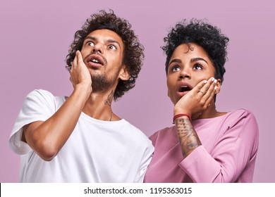 Wow, what is on floor Surprised young dark skinned male and female couple keep hands on cheeks, looking up with amazed face expressions how grew their bills, pose against lavender background