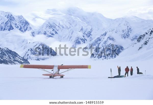 WRANGELL MOUNTAINS, WRANGELL, ALASKA  - CIRCA 2001: Mountain climbing team and airplane in Wrangell Mountains in St. Elias National Park and preserve, Alaska