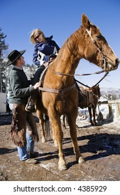 Wrangler talking to woman on horse.