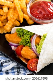 Wrap with fried Chicken (close-up shot) and chips