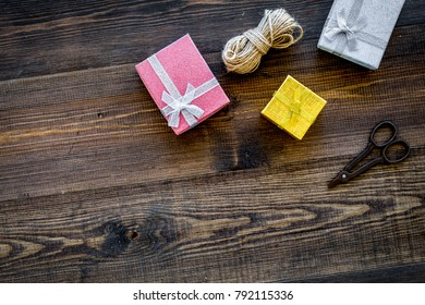 To wrap gift. Boxes, thin cord, sciccors on wooden background to