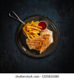 Wrap with grilled chicken served with chili sauce and french fries