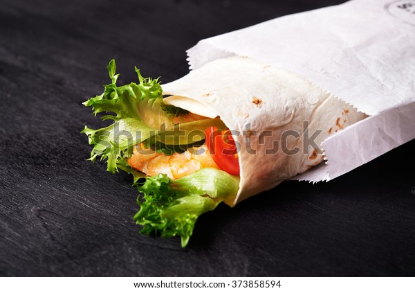 wrap with prawn, tomatoes and lettuce in paper bag