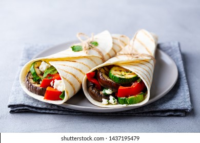 Wrap sandwich with grilled vegetables and feta cheese on a plate. Grey background.