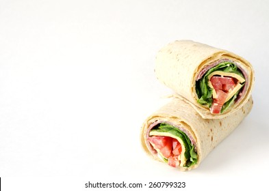 wrap sandwich with salami, lettuce, tomatoes and cheeses on white background with copy space.