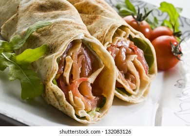 Wrap sandwich with salmon and vegetables on a white plate