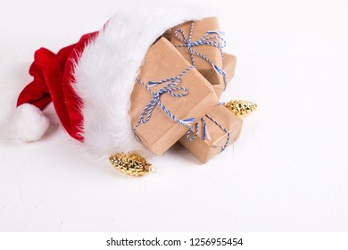 Wrapped boxes with presents  and decorative golden pine cones in Santa hat on white textured background. Selective focus. Place for text. Winter holiday, Christmas, New Year.