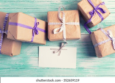 Wrapped boxes with presents  and empty tag on turquoise painted wooden planks. Selective focus is on tag. Place for text.