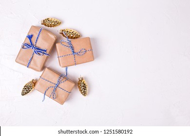 Wrapped boxes with presents and golden decorative pine cones on white textured background. Top view.  Flat lay. Winter holiday, Christmas, New Year.  Place for text.