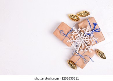 Wrapped boxes with presents, snowflake and golden decorative pine cones on white textured background. Top view.  Flat lay. Winter holiday, Christmas, New Year.  Place for text. Selective focus.