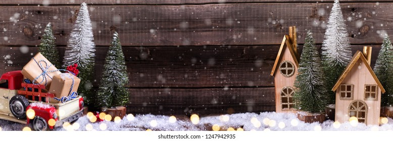 Wrapped boxes in red car, decorative houses and fir trees  on aged wooden background. Winter holidays decoration. Drawn snow effect. Selective focus. Place for text. Long banner format.