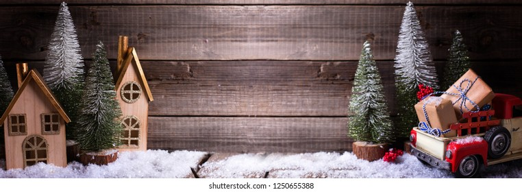 Wrapped boxes in red car, decorative houses and fir trees  on aged wooden background. Winter holidays decoration. Selective focus. Place for text. Long banner format.