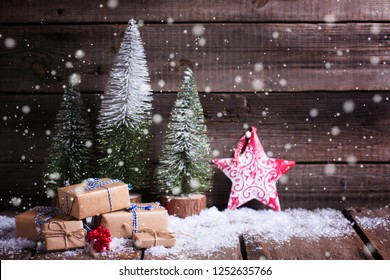 Wrapped boxes, red decorative star and fur trees  on aged wooden background. Winter holidays decoration. Selective focus. Place for text.