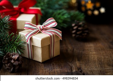Wrapped Christmas gifts on dark rustic wooden table with pine cones and fir branches. With copy space for your text