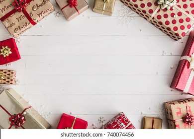 Wrapped Christmas gifts on a white wooden background, overhead shot