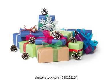 Wrapped Christmas presents with bows, pine cones and silver snowflake. Isolated over white background