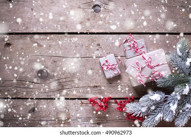 Wrapped christmas presents, fur tree branches, red berries on vintage wooden background. Selective focus. Place for text. Drawn snow.