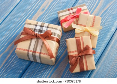Wrapped colorful gifts with ribbons for Christmas, Valentine, birthday or other celebration lying on old boards