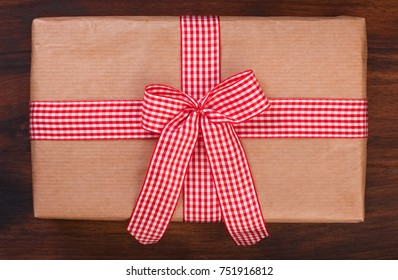 Wrapped gift box with red and white checkered ribbon bow on a dark walnut wood, top view, close up