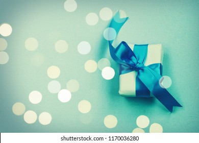 wrapped gift box with silk bow, on paper texture background, holiday birthday, father day concept, defocused light