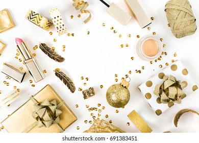 wrapped gift boxes and makeup cosmetics kit over white background, still life in golden colors with copy spase