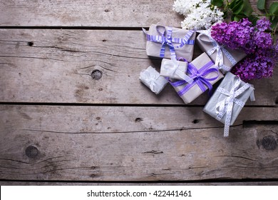 Wrapped  gift boxes with presents  and lilac flowers on aged wooden background. Selective focus. Place for text.