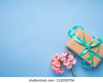 Wrapped gift and pink flowers flat lay. Gift for mother woman day, wedding, valentine concept