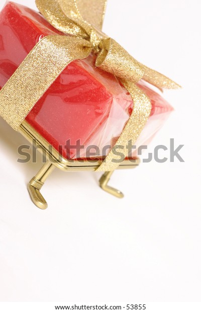 wrapped gift tied with metallic gold bow, angled perspective
