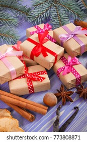 Wrapped gifts with colorful ribbons for Christmas time or other celebration, spices for cooking and spruce branches on old boards
