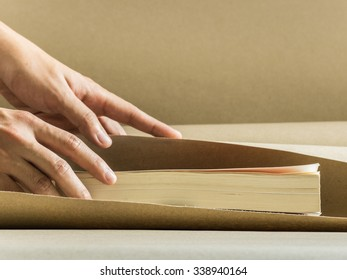 Wrapping a book with brown paper