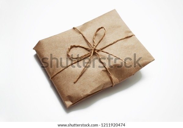Wrapping brown craft paper package with hemp as present. Hand made parcel bag gift. Isolated on white background.