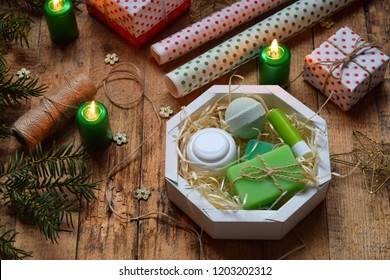 Wrapping cosmetic gift - body cream, bath bomb, soap, lipstick. Composition with present box, packing paper, festive decoration and fir tree branch. Merry Christmas and Happy New Year concept