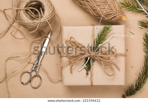 Wrapping eco Christmas packages with brown paper, string and natural fir branches