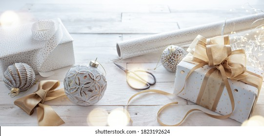 Wrapping festive christmas gift. Gift box with golden ribbon bow and Christmas balls on white wooden vintage background. Background with short depth of field and bokeh for christmas season.