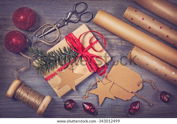 Wrapping paper and a gift on a wooden background