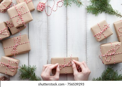 Wrapping presents and gift boxes in kraft paper with fir tree decorations on white wooden background, copy space
