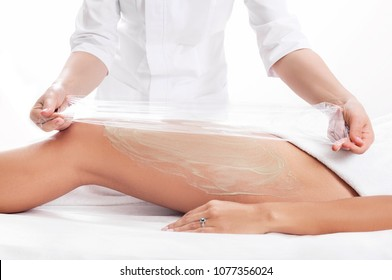 wrapping procedure by a cosmetologist - a cellulite mask