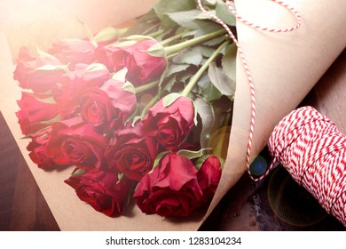 Wrapping Valentine's Day red roses in brown paper on dark wood background with lens flare.