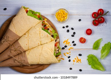 Wraps with chicken, tomatoes, lettuce, black beans, cheddar cheese and sweet corn. Tortilla, burritos, sandwiches twisted rolls. View from above, top, horizontal