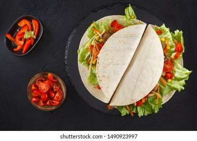 Wraps with chicken and vegetables on black slate. Chicken stuffed tortilla, Mexican food