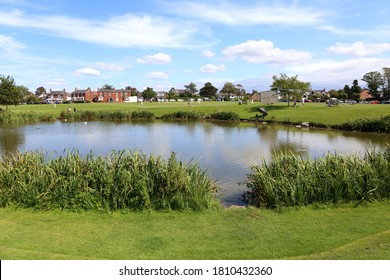 Wrea Green, Lancashire, UK - August 8 2020: Cricketers play a game on the village green beyond the duck pond on a summers day in August, 2020.