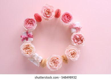 Wreath of beautiful pink tone rose flowers, macaroons and gift boxes on pastel pink background,top view