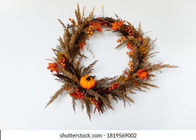 A wreath of branches, decorated with berries, orange leaves, pumpkin and dried flowers. Autumn, harvest or Halloween concept, isolated on white background.