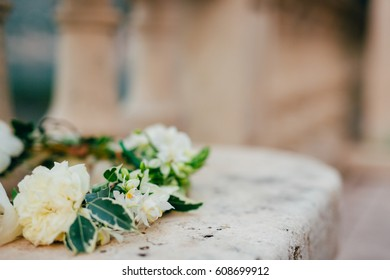 Wreath Bride of white flowers on old stone bench.