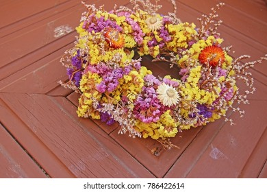 Wreath with different flowers on a wooden door