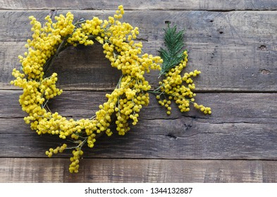 Wreath of flowers and acacia branch on rustic wooden background. Acacia dealbata. Space to write. womens day, mothers day, spring concept. Top view, flat lay