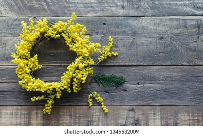 Wreath of flowers and acacia branch on rustic wooden background. Acacia dealbata. Space to write. spring concept.  Top view, flat lay.