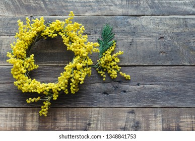 Wreath of flowers and acacia branch on rustic wooden background. Acacia dealbata. womens day, mothers day, spring concept. Flat lay, Top view, copy space