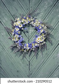 Wreath of flowers on the old wooden background. Wildflowers on a sunny day. With retro filter effect