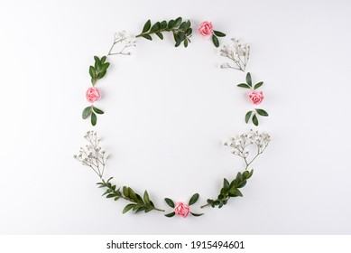 Wreath frame made of flowers branches, eggs and shells on a white background, top view, flat lay, close up. Easter background.